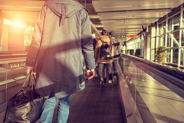 Menschen mit Handgepäck am Flughafen