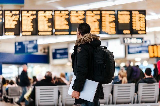Mann mit Rucksack vor Flughafen Anzeige