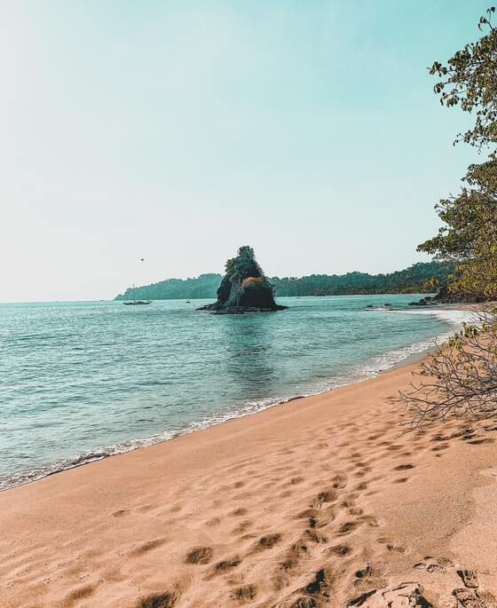 Secluded and quiet beach overlooking large rock in the water