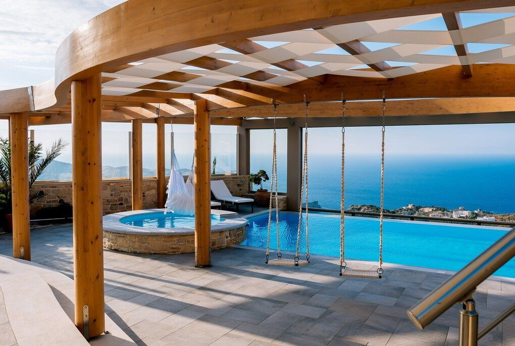Pool with swings underneath wooden pergola overlooking the ocean in Crete