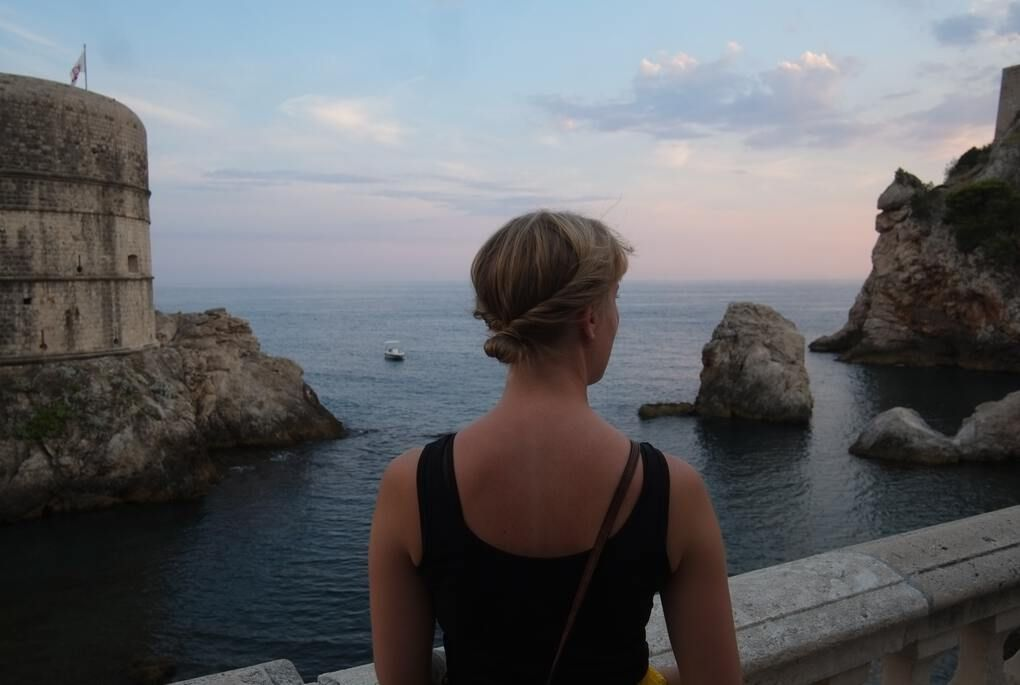 Girl overlooking the ocean with a castle and rocks on either side in Dubrovnik