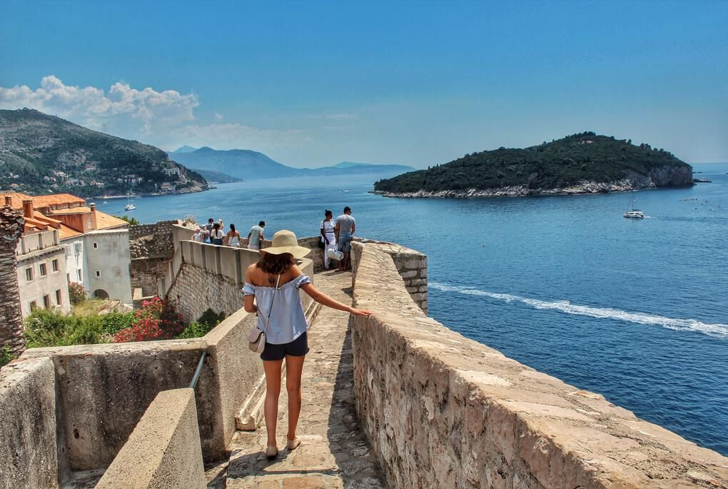 Girl walking along city walls in Dubrovnik