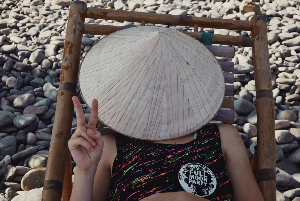 Girl relaxing with hat on face and full moon party sticker