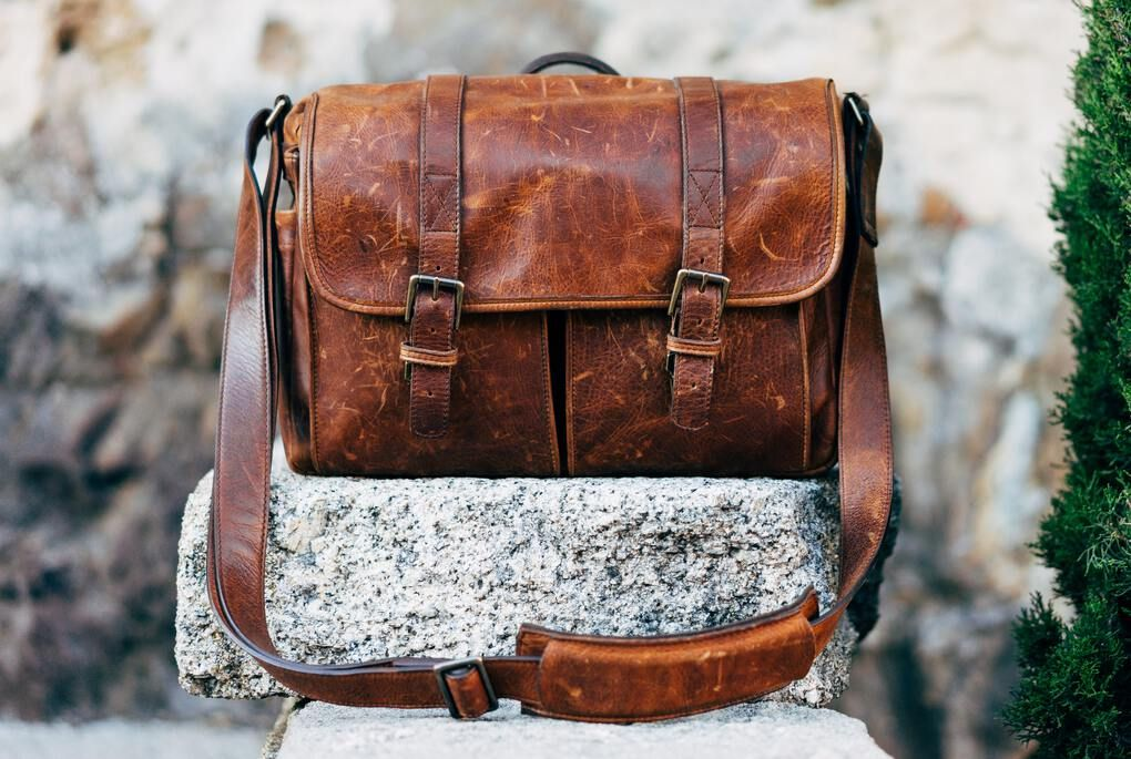 Brown leather camera bag sitting on a rock