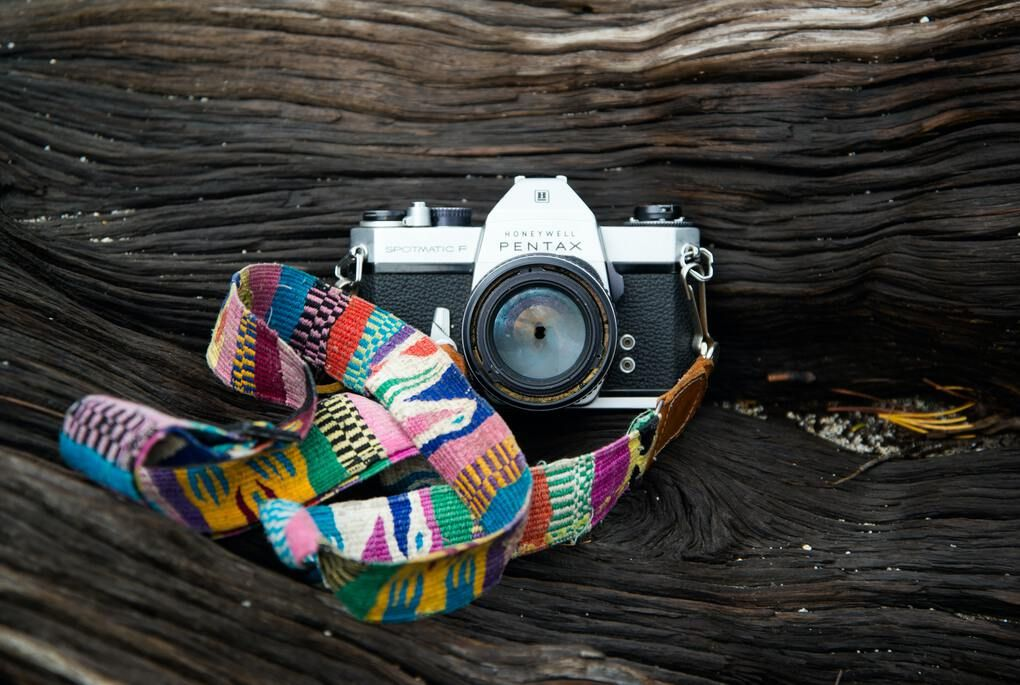 Multi-colored camera strap attached to black camera