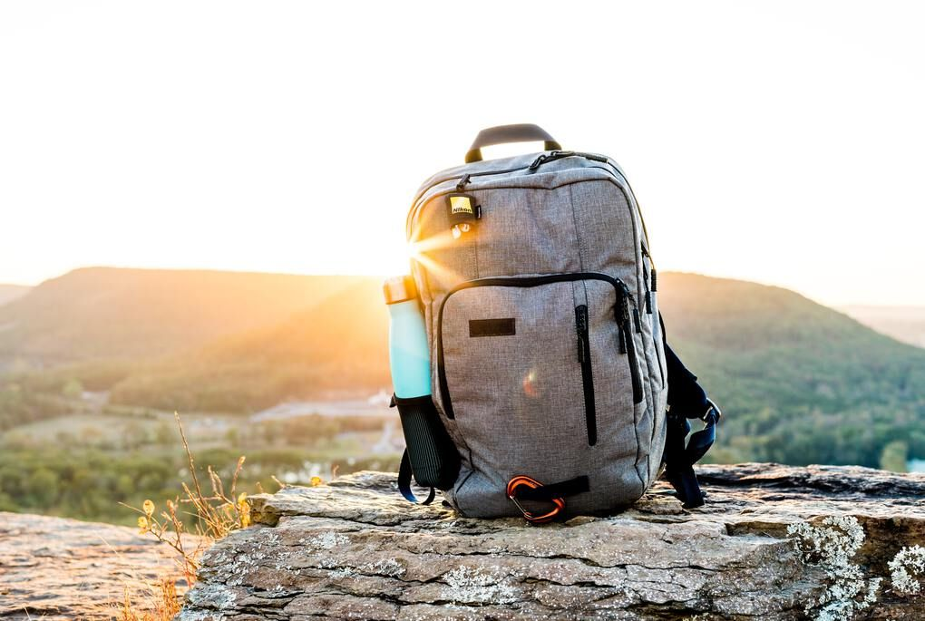 Gray travel backpack on a rock overlooking the mountains