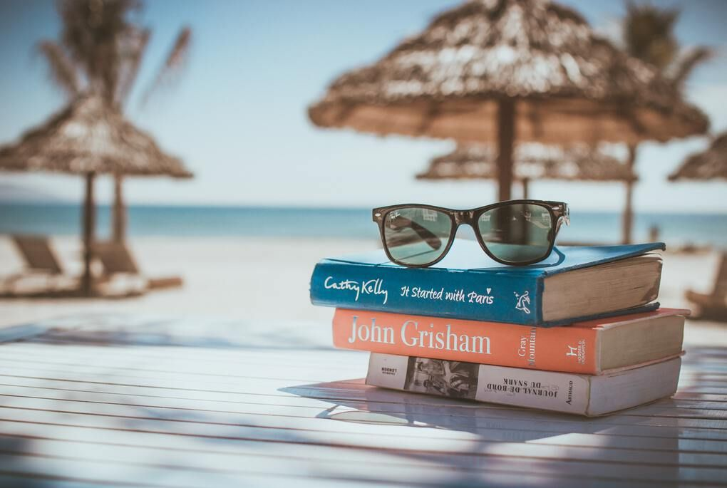 Stack of three books on the beach with cabanas in the background