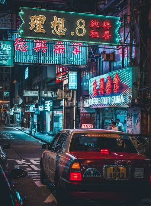 Hong Kong at night with neon signs and taxi