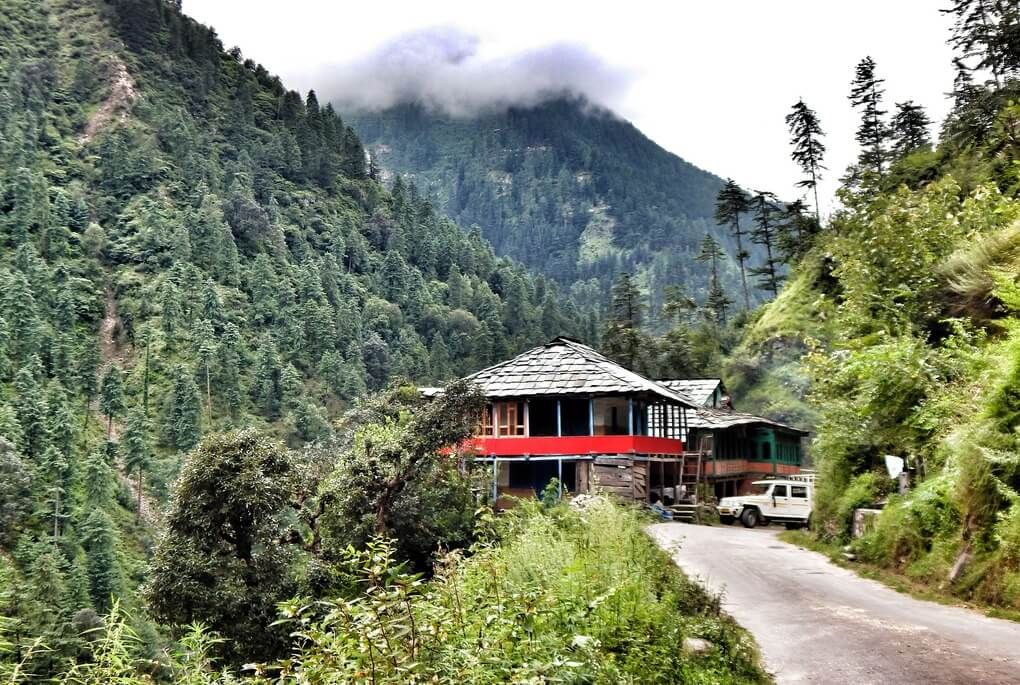 Shack surrounded by lush green mountains in the valley of the Great Himalayan National Park