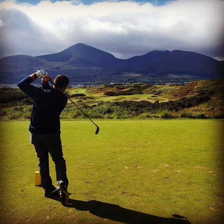 Man golfing on green golf course in Ireland