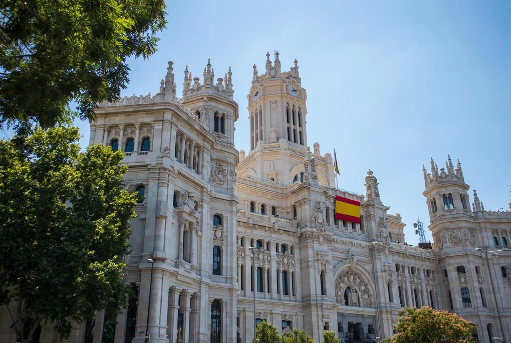 Plaza de Cibeles displaying Spanish flag in Madrid Spain