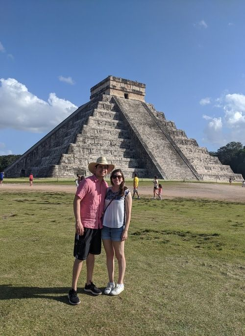 Couple standing in front of Chichen Itza pyramid in Mexico