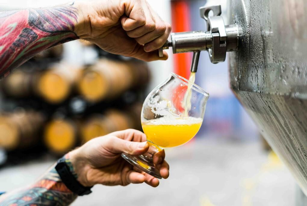 Milwaukee Brewery Tour - man with tattoos pouring beer from a tap