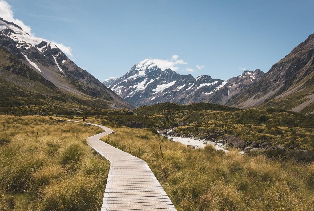 Wooden pathway through the valley between snow covered mountains