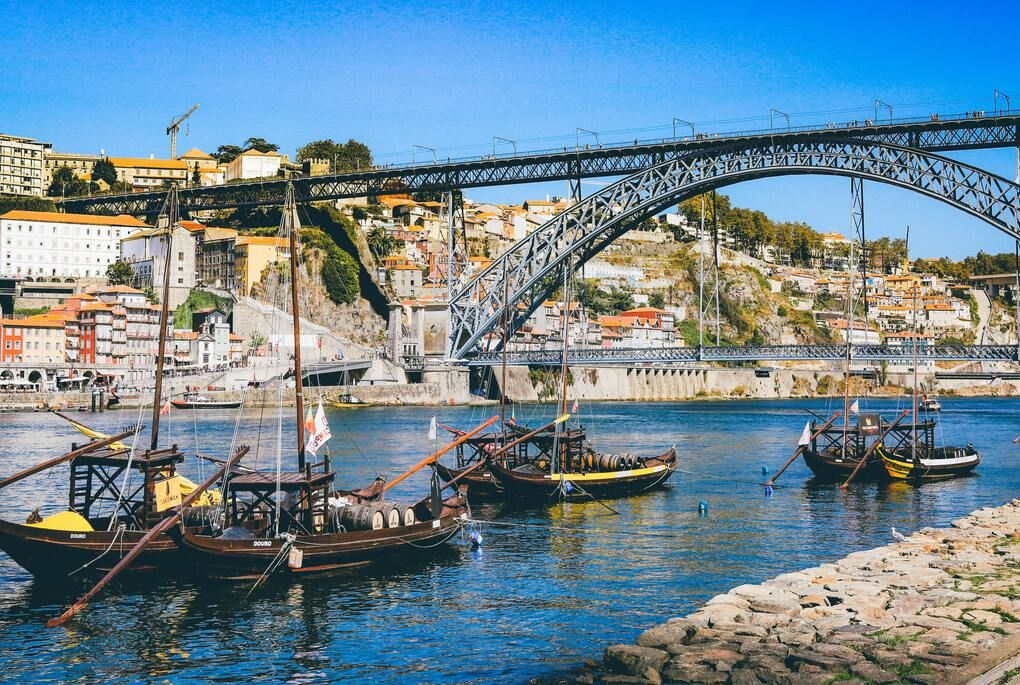 Boats on the Douro River in front of the Dom Luis I Bridge