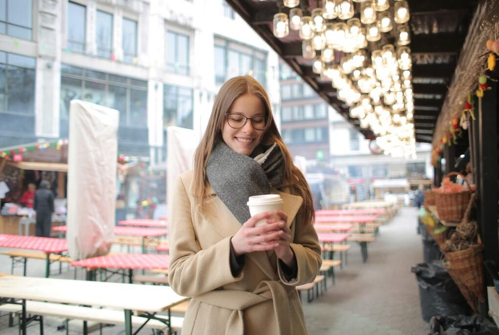 Woman in brown coat holding white coffee cup