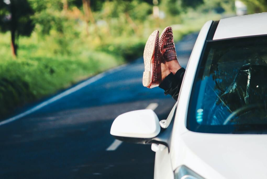Feet hanging out of the window on a road trip