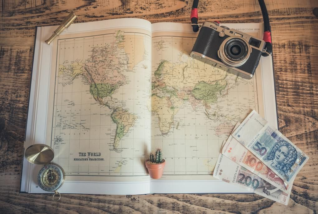 Planning a trip with a map, camera, and money