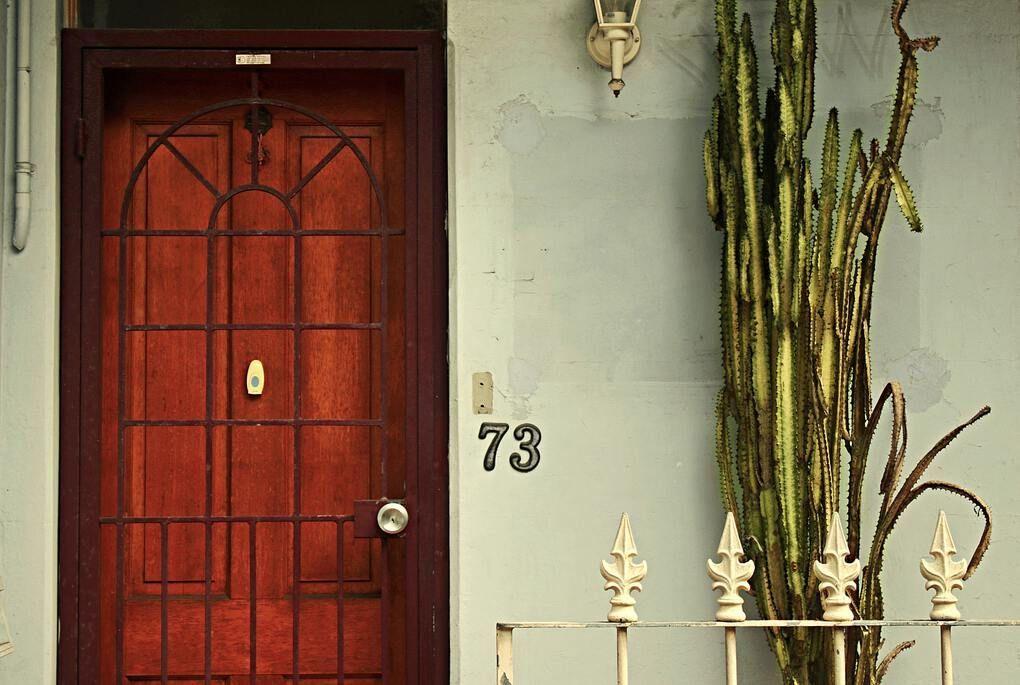 Red door with metal balcony in Paddington