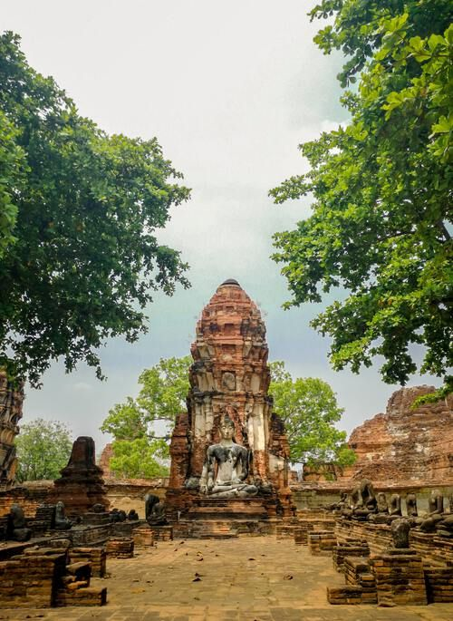 Ancient rocky temple framed by green trees