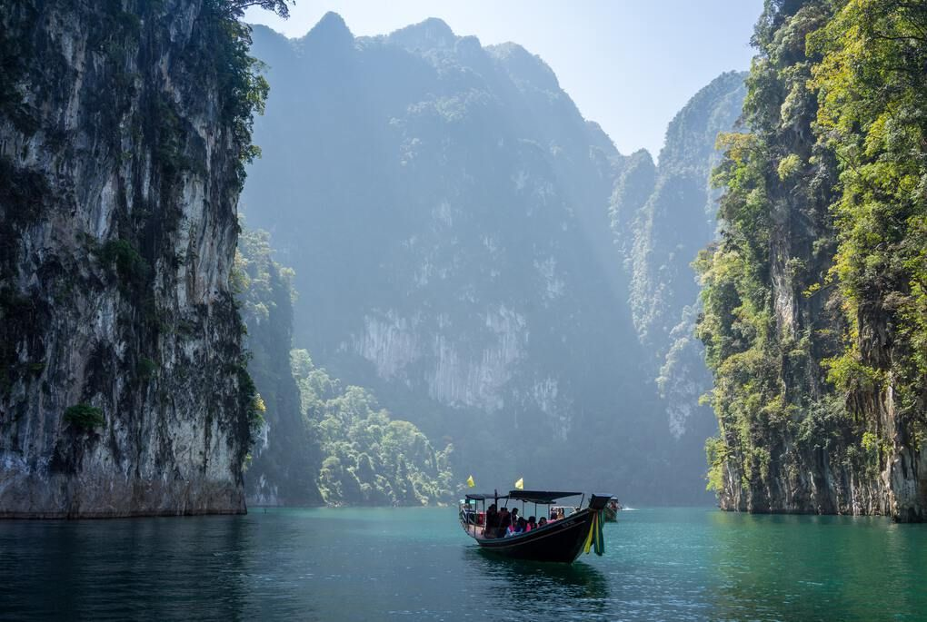 boat in turquoise water surrounded by mountainous cliffs