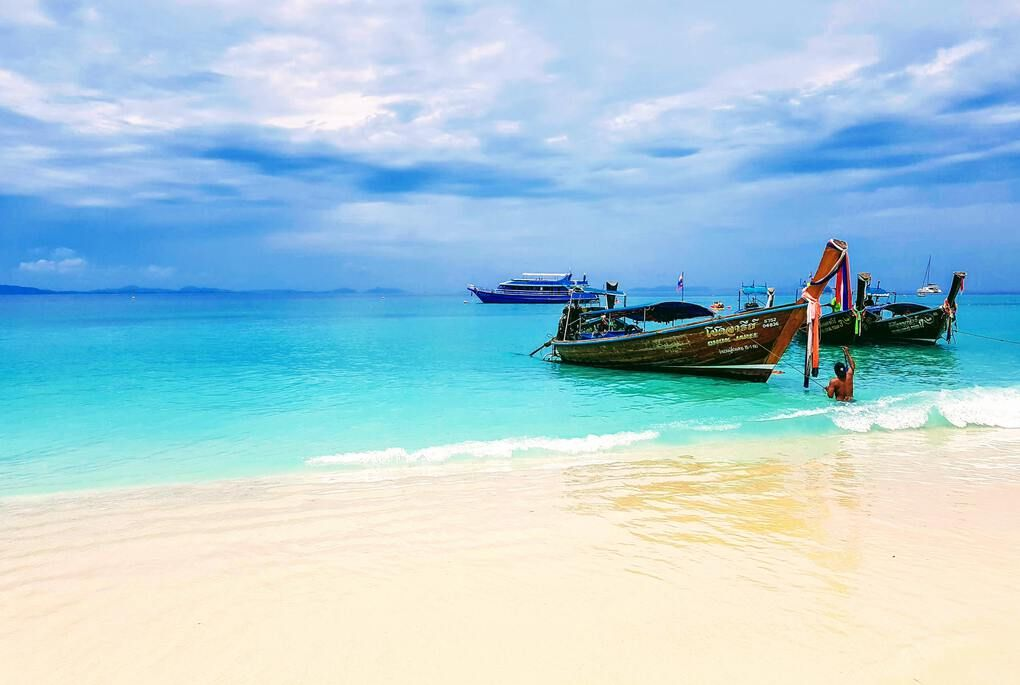 Boat on beautiful blue water and white sandy beach