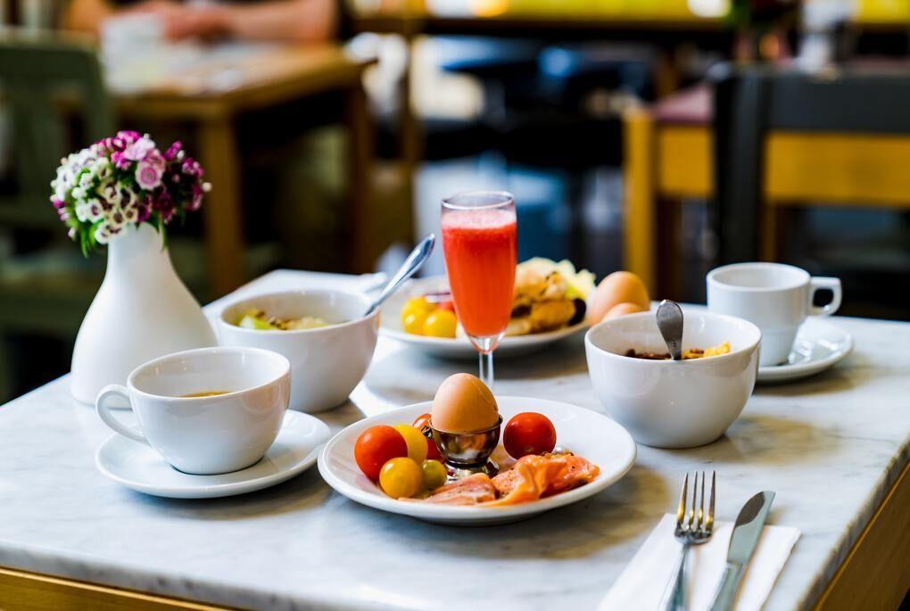 Petit-déjeuner complet avec café et vase de fleurs
