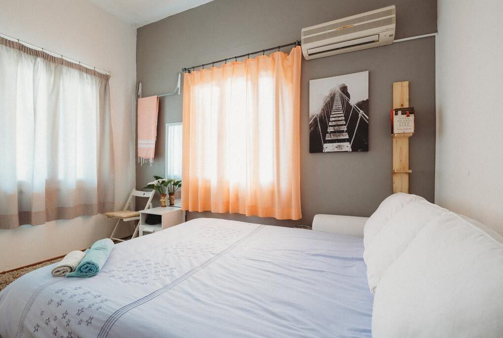 Chambre d'hôtel confortable avec lit blanc et rideaux tirés