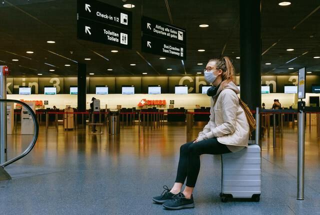 Girl wearing mask sitting on suitcase in the airport