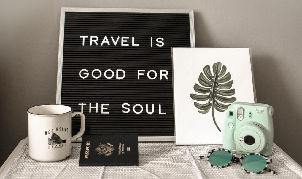 Travel is the good for the soul on black board with camera, mug, leaf print, and passport