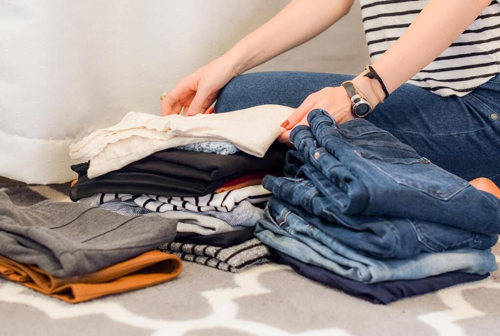 Woman packing her clothes, jeans and shirts