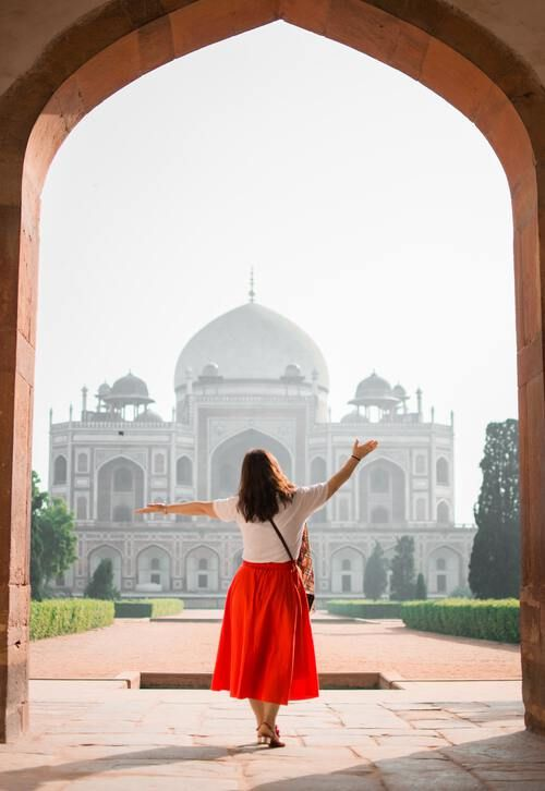Woman in red skirt in front of beautiful religious building