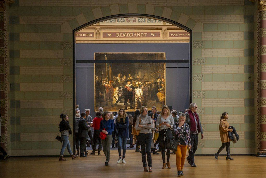 People standing in front of the Nights Watch by Rembrandt at the Rijksmuseum
