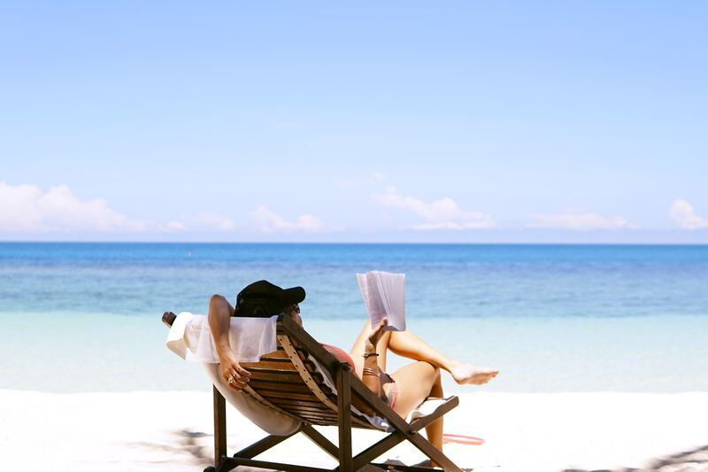 woman reading on the beach in a chair