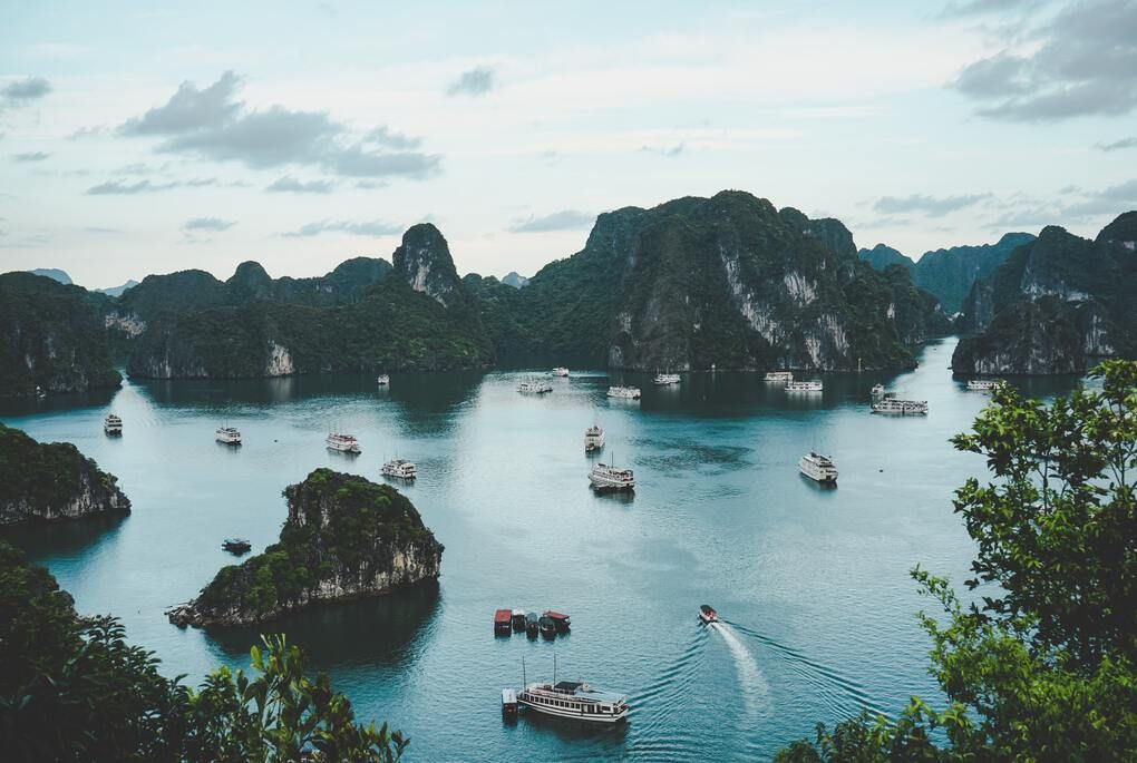 Looking down on mountains and boats in the water in Vietnam
